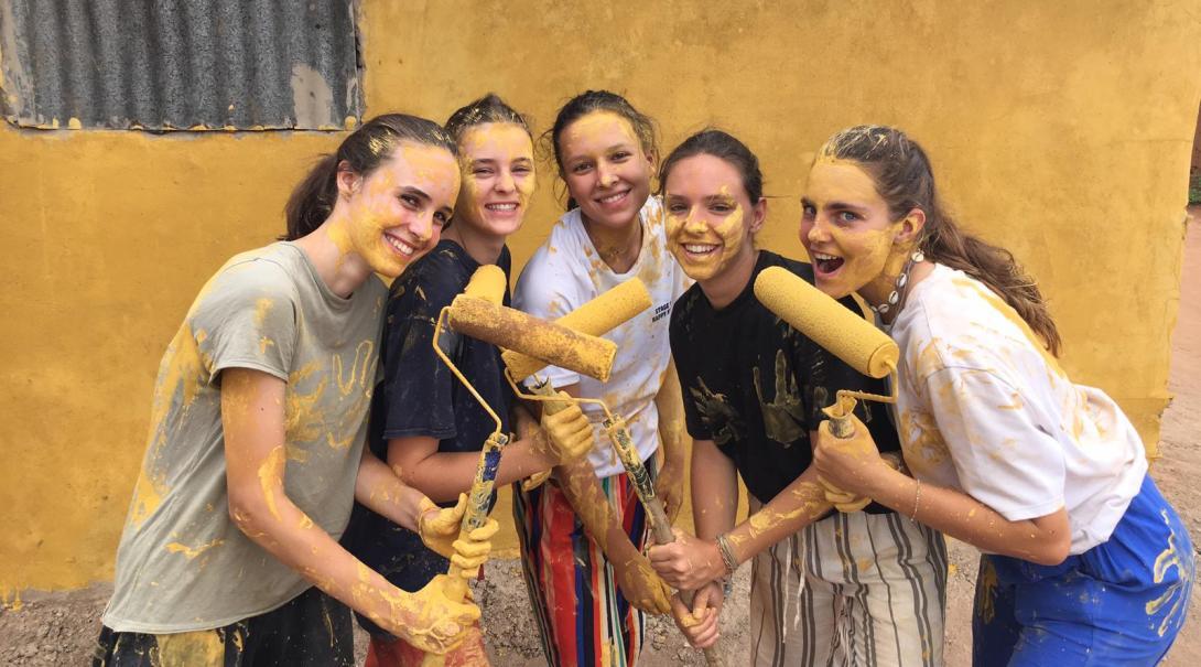 Fem kvinnliga ungdomsvolontärer som målar under deras volontärresa utomlands.